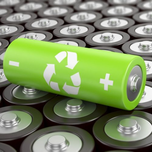 Battery recycling concept. Green battery with recycling symbol, surrounded by other batteries.
